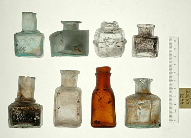 14. Small glass bottles and an inkwell.